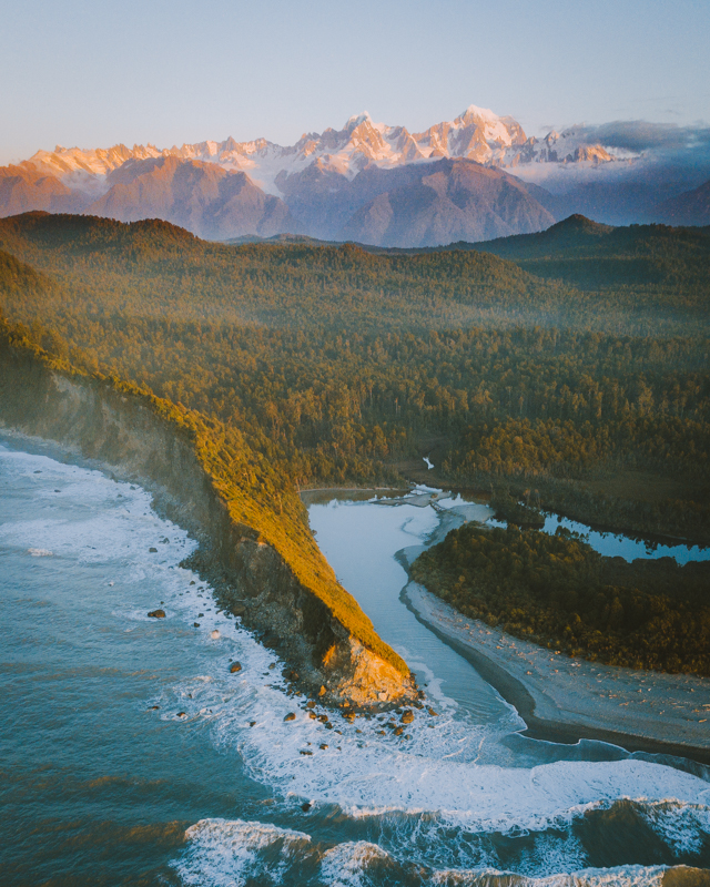 A Drone Shot Of The Wild Coastline With The Southern Alps In The Background
